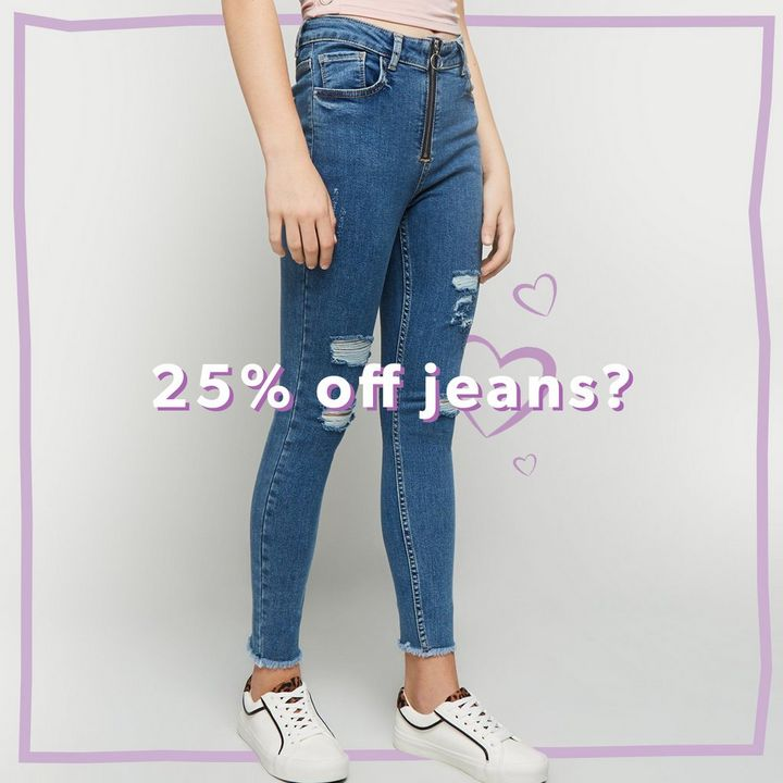 25% off Jeans. Model wears high waisted ripped jeans in blue with white trainers