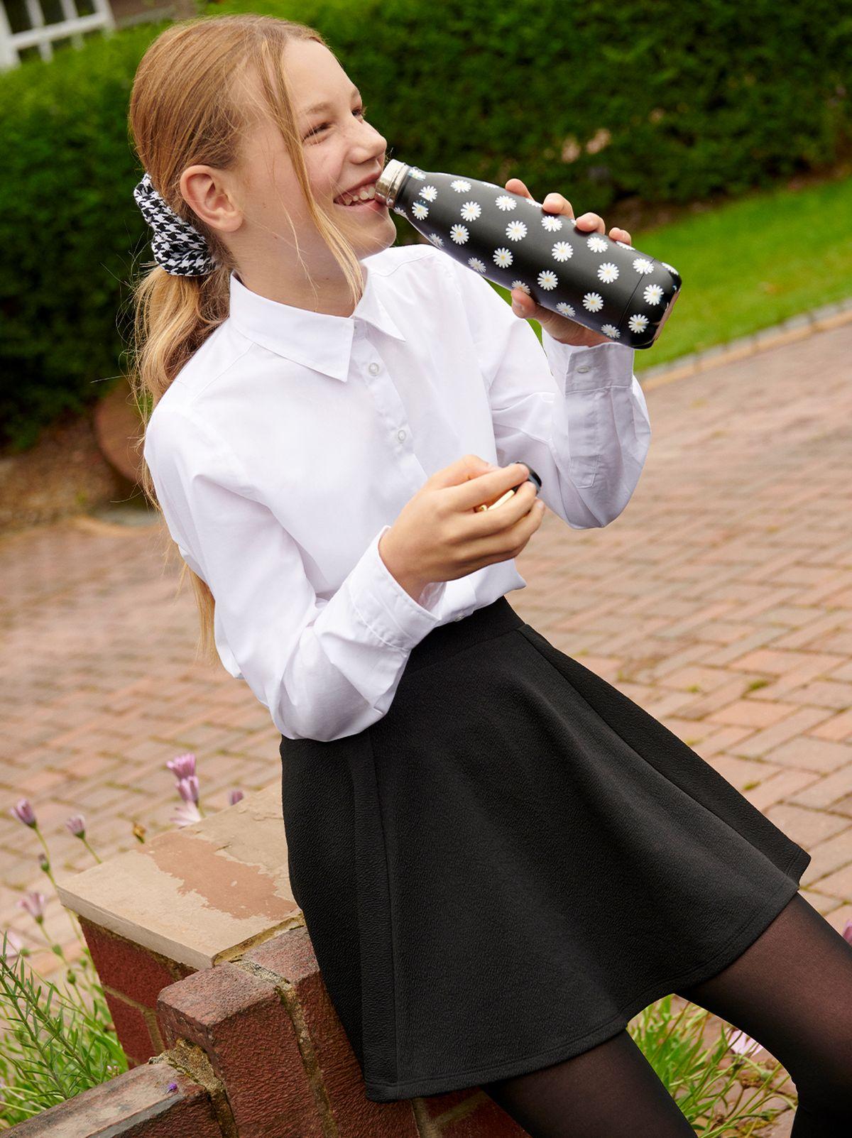 Girl in her school uniform drinking from her black daisy water bottle.