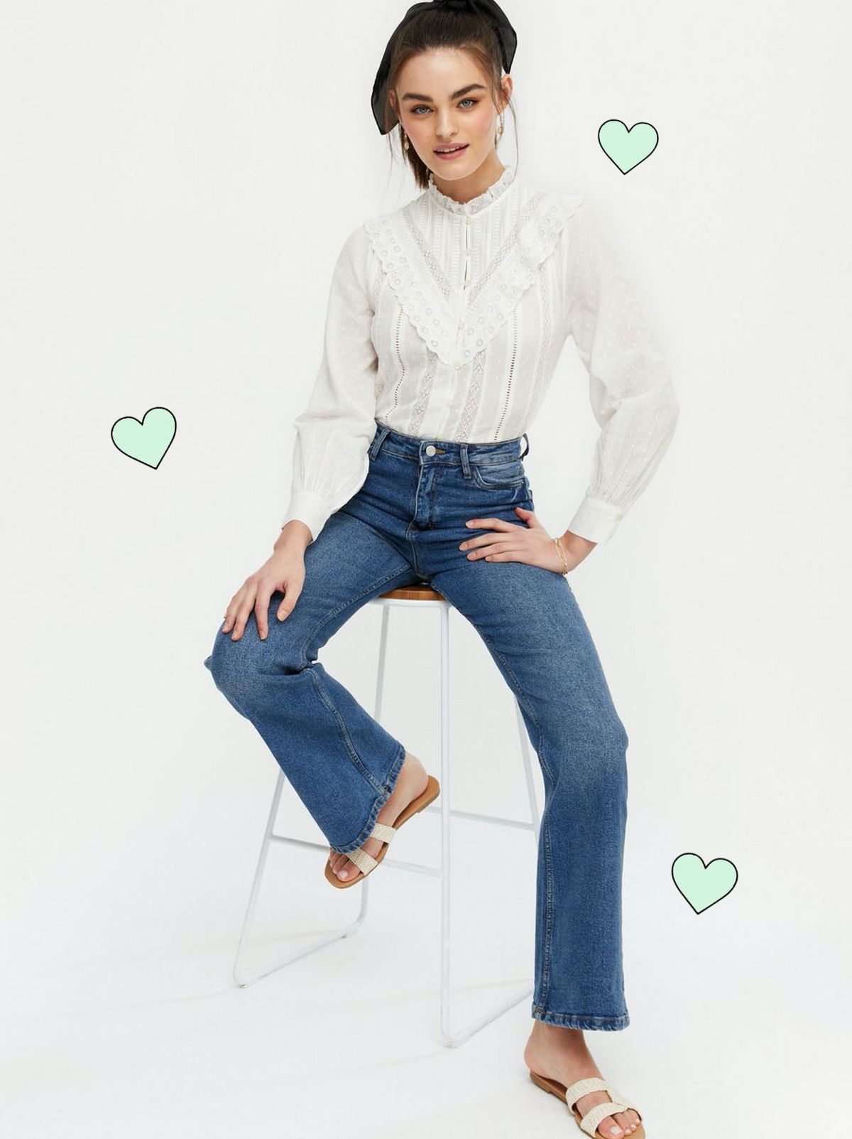 Woman wearing an off white high neck shirt, blue jeans and sliders
