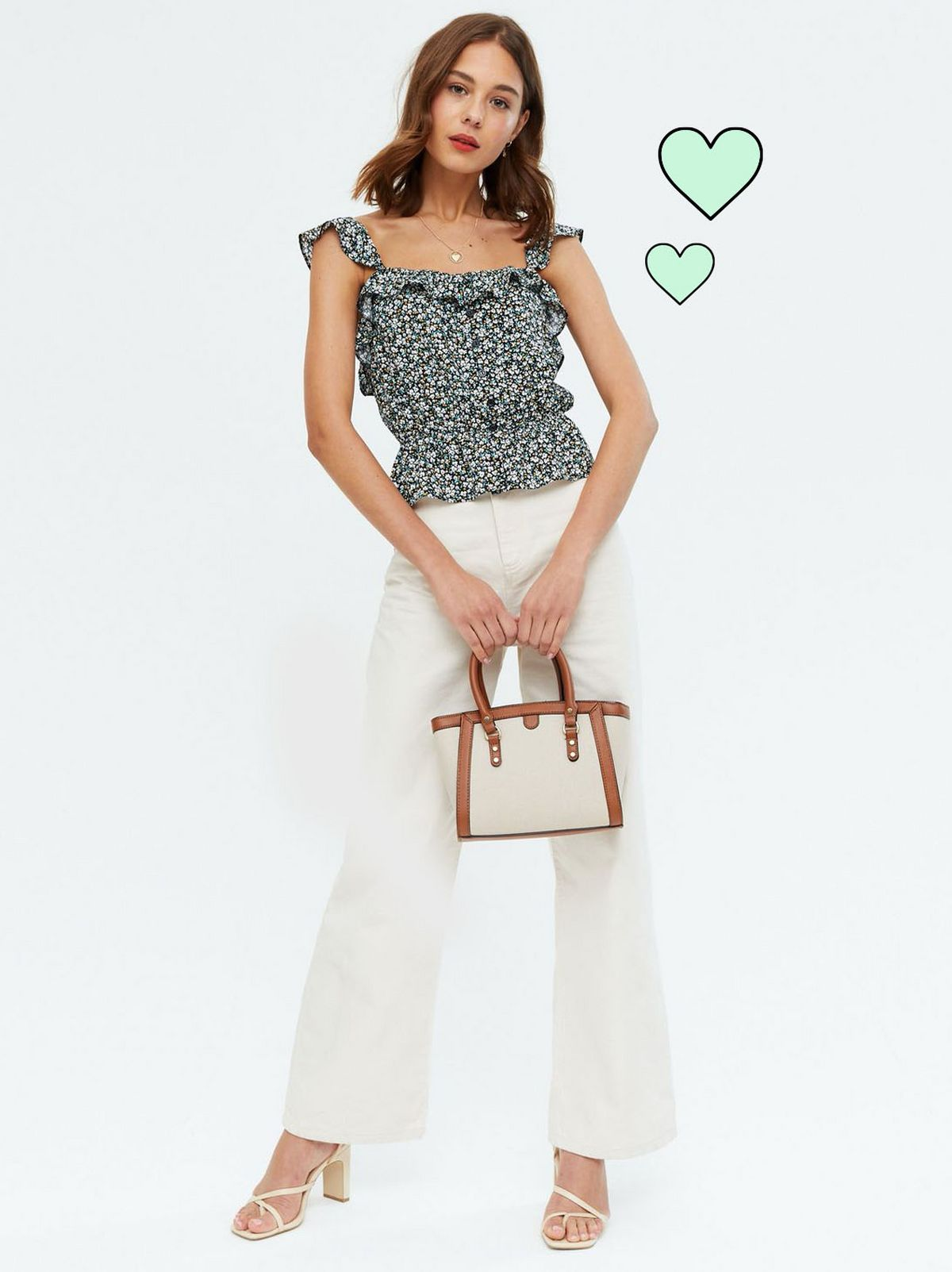 Woman wearing a black floral frill cami top, white flare trousers and heels