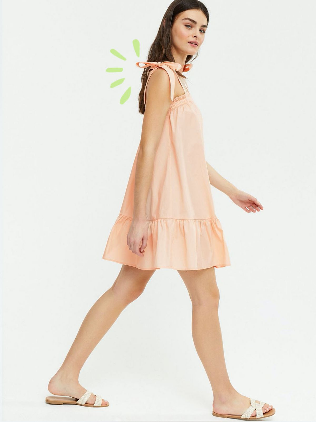 Woman wearing a Coral Tie Strap Tiered Mini Sundress.