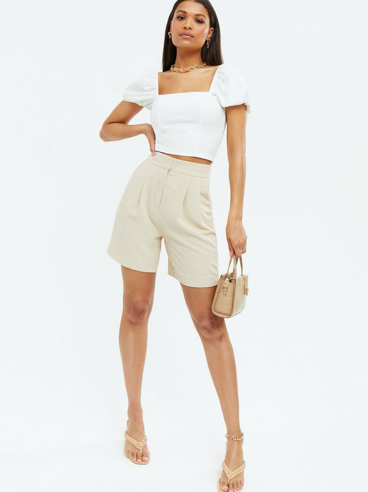 Woman wearing a white puff sleeve lace up back crop top, cream shorts and heels