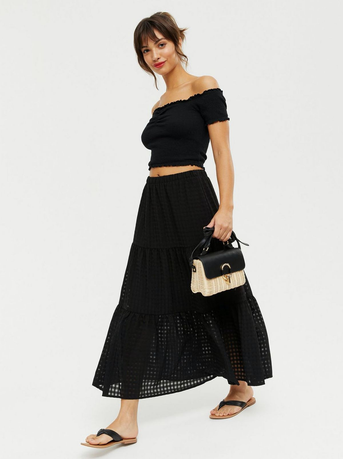 Woman wearing a black gingham high waist tiered midi skirt, black off shoulder top and sliders