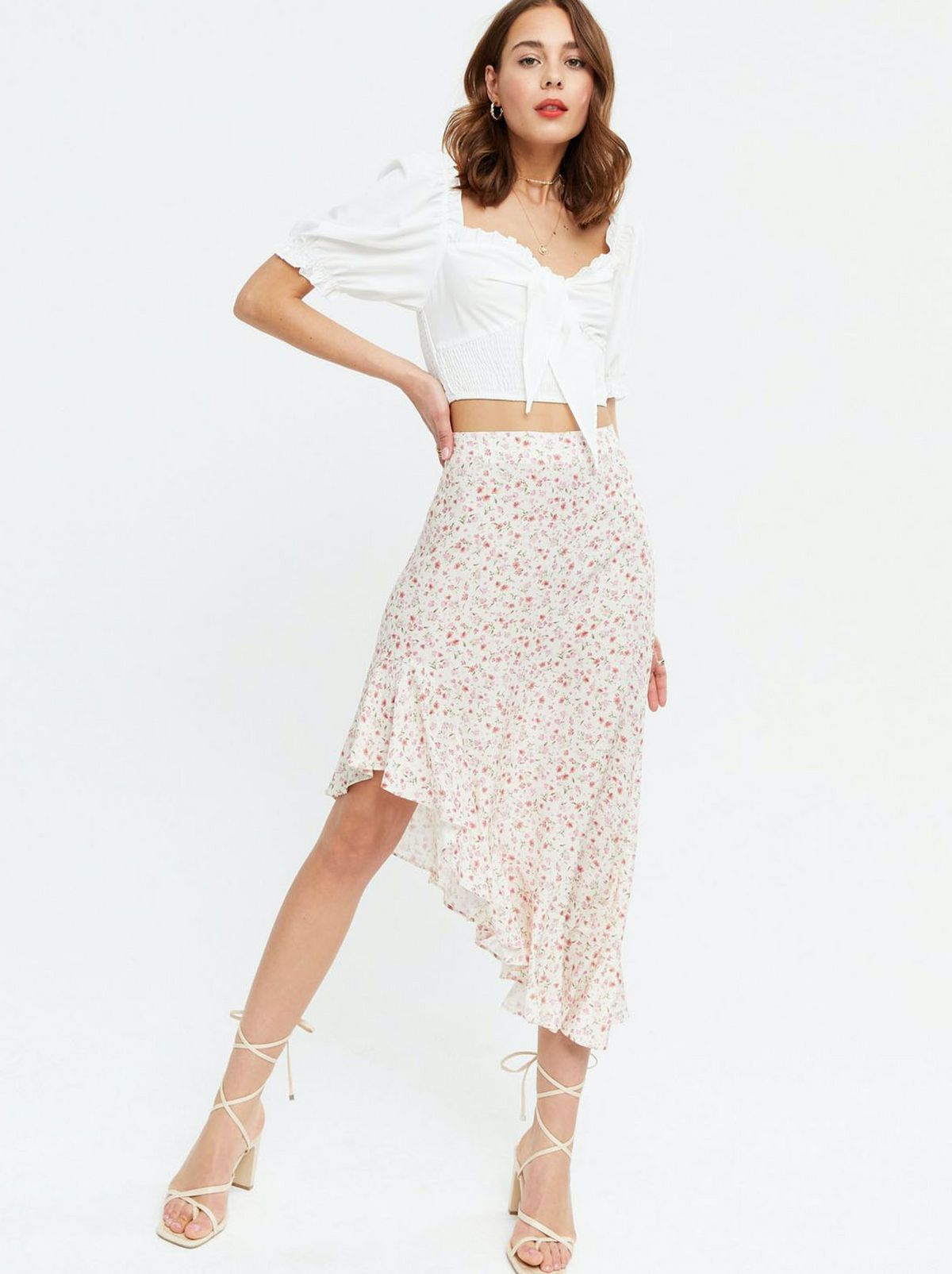 Woman wearing a white ditsy floral midi skirt with a white puff sleeve top