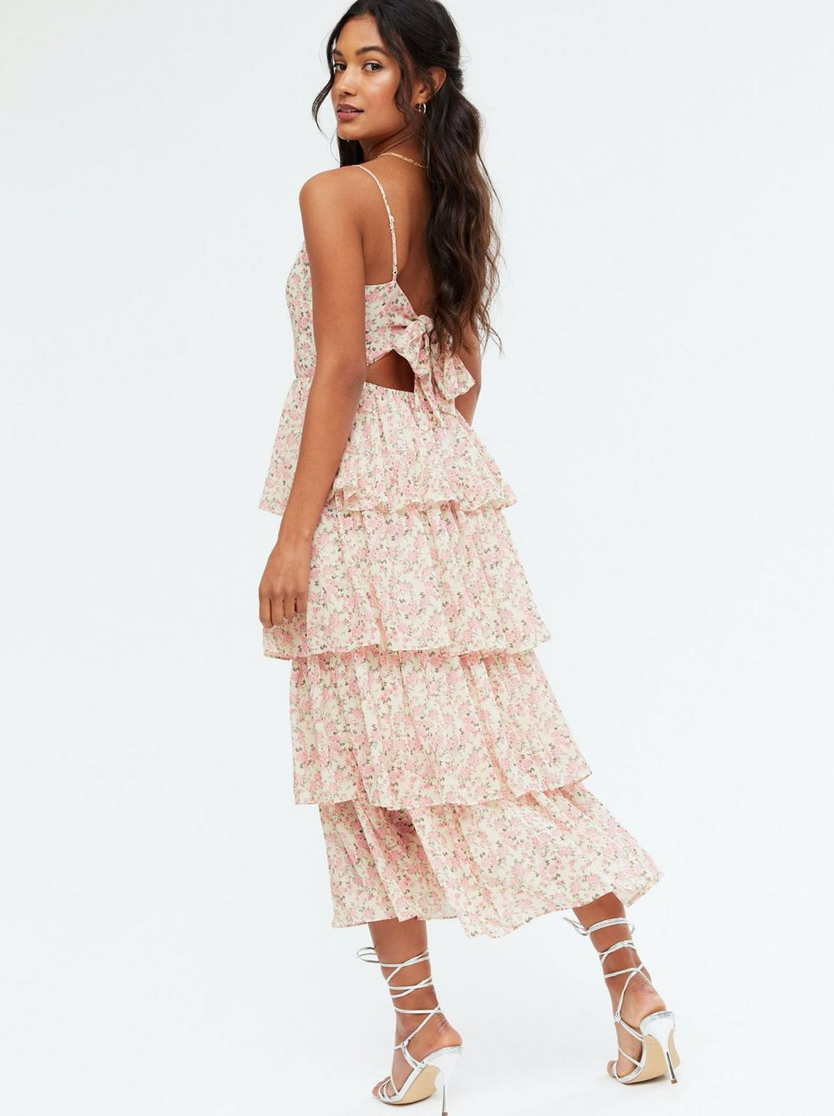 Woman wearing a pink ditsy floral tiered tie back midi dress and strappy heels
